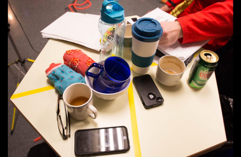 Une table de répétition lambda chez La Pire Espèce : du café, des chaussettes, des machins électroniques, une table fluorescente, du café...